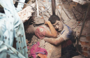 A couple holding each other while collapsed under Rana Plaza.
