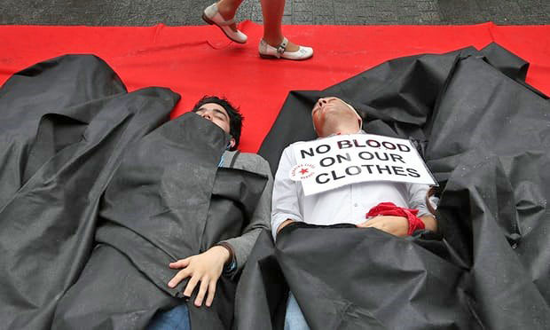 Figure 2: Activists protest in Brussels on the first anniversary in 2014 of Bangladesh's Rana Plaza factory collapse. (Credit: Francois Lenoir/Reuters)
