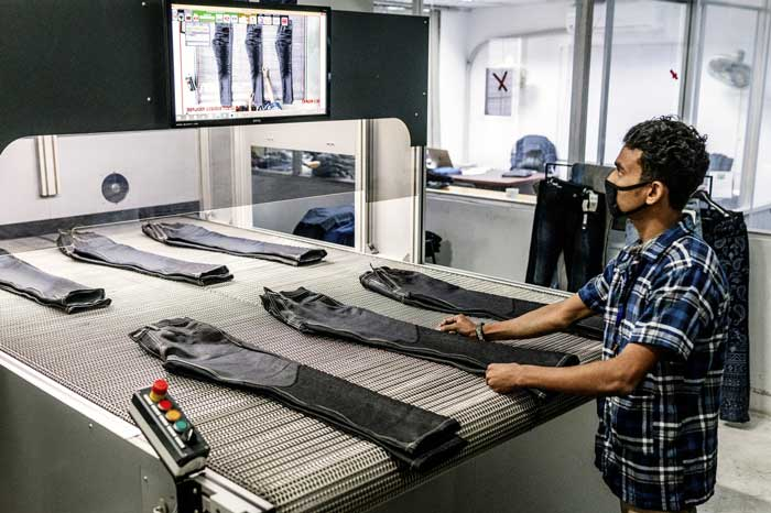 A worker uses a laser-engraving machine to distress jeans at Denim Expert Ltd