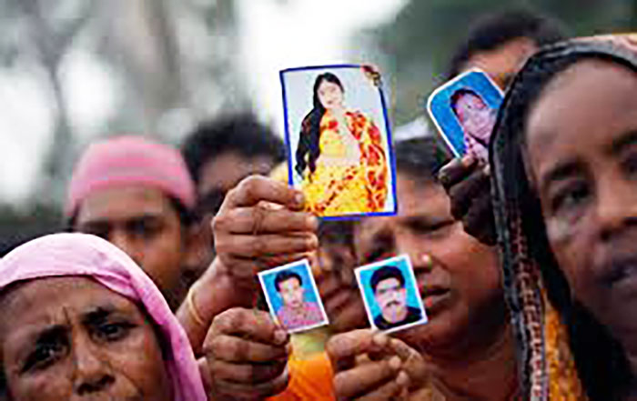 Activists hold up photographs of their missing relatives-who worked at Rana Plaza-outside of Dhaka